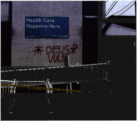 "The phrase ""Deus Vult"" spray-painted in red letters on a Planned Parenthood facility in Newark by Samuel Gulick."
