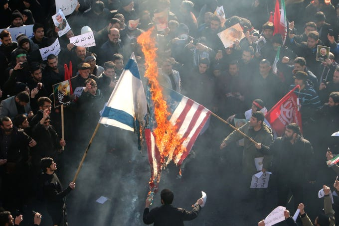 Iranians set a U.S. and an Israeli flag on fire during a funeral procession organized to mourn the slain military commander Qasem Soleimani, Iraqi paramilitary chief Abu Mahdi al-Muhandis and other victims of a U.S. attack in the capital Tehran on Jan. 6, 2020.  Mourners packed the streets of Tehran for ceremonies to pay homage to Soleimani, who spearheaded Iran's Middle East operations as commander of the Revolutionary Guards' Quds Force and was killed in a U.S. drone strike on Jan. 3 near Baghdad airport.