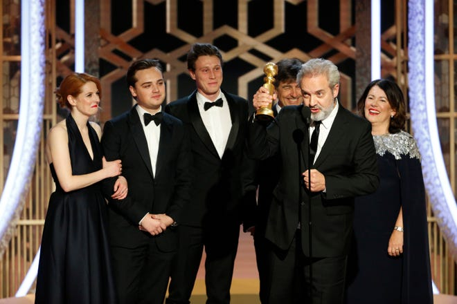 Director Sam Mendes (front) accepts the award for best drama with cast and fellow filmmakers at the 77th Golden Globes.
