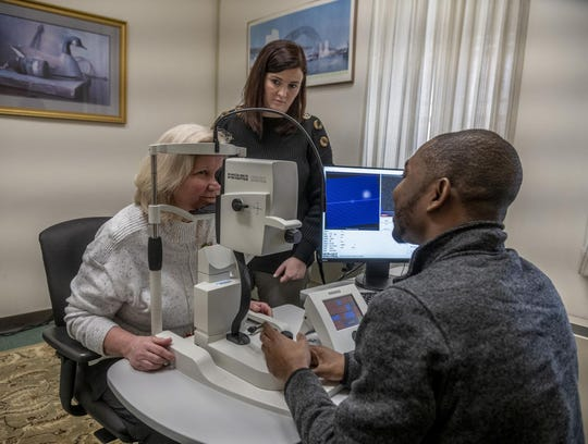 Jessica Alber, Ph.D., Ryan research assistant professor of neuroscience at University of Rhode Island, standing, and Edmund Arthur, seated at right, doctor of optometry and member of Alber's lab, work with a Butler Hospital nurse in preparation for a clinical trial using retinal scans to detect early signs of Alzheimer's disease.