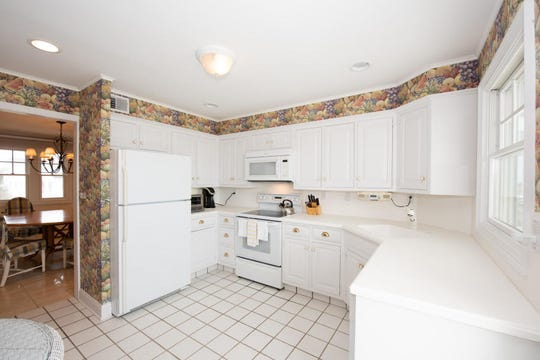 The kitchen offers all white custom cabinetry and appliances.