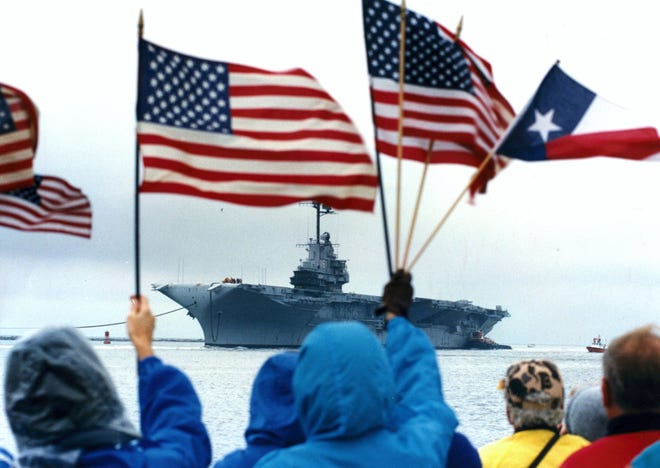 People line the Port Aransas jetties as the USS Lexington enters the Coprus Christi Ship Channel on January 29, 1992. Corpus Christi was awarded the decommissioned aircraft carrier and turned it into a floating museum.