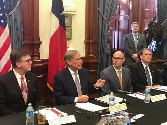 Texas Gov. Greg Abbott, center, speaks to reporters at the Capitol, Jan. 7, 2020.