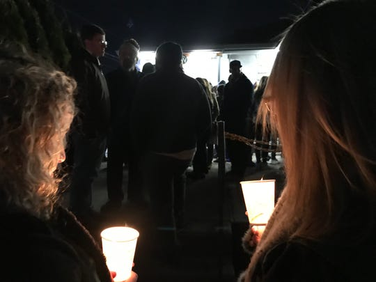 Candles flicker at a vigil outside the Shamrock Deli in Audubon on Monday night.