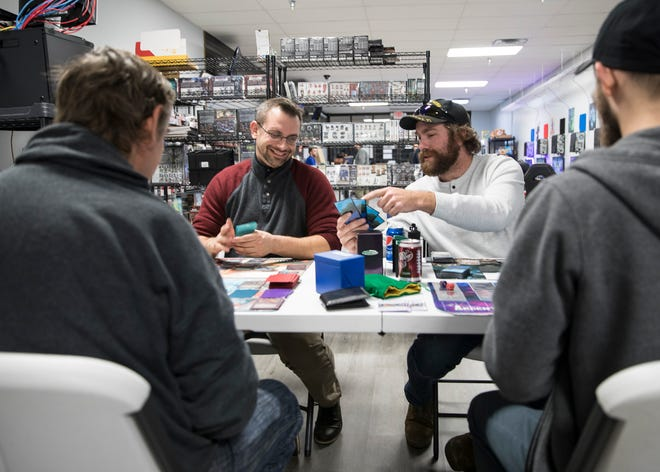 Russ Nichols, right, shows his Argent Saga card hand to Chris McCoy as both men play the popular, action trading card game at the Total Gaming Experience esports arena in Chillicothe on Monday, Jan. 6, 2020.
