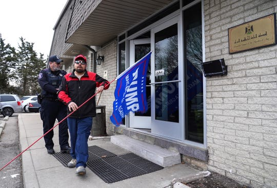 A Southfield, Michigan, police officer stands by Jan. 7 as Michael Curtis of Eastpointe walks out of the Consulate General of the Republic of Iraq in Detroit, carrying his flag in support of President Trump. The consulate was accepting condolences for Iranian Major Gen. Qasem Soleimani and Cmdr. Abu Mahid Al-Mohandes, killed in a U.S. airstrike in Baghdad.