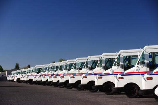 A fleet of US postal service vehicles parked in a line.