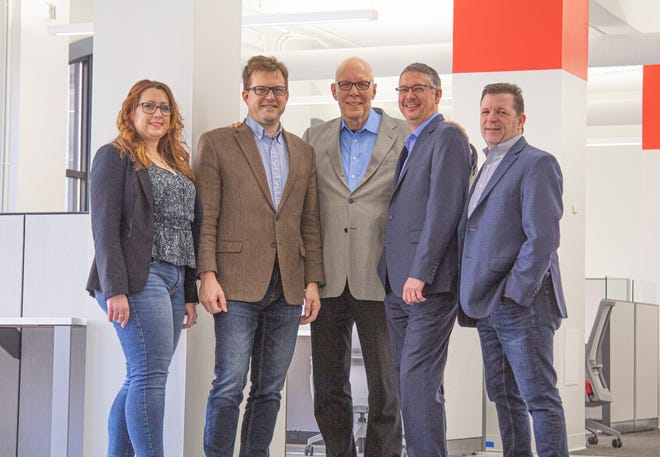 MCCI's executive team poses in the 4,000 sq. ft. expansion of its downtown Detroit headquarters. From L to R: Jennette Smith Kotila, chief marketing officer; Christopher Heaton, CEO; Terrence Oprea, outgoing president and CEO; Richard Donley, APR, president; Todd Haight, chief strategy officer.