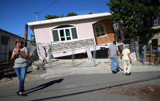 Residents survey damage where a home partially collapsed after an earthquake hit Guanica, Puerto Rico, Monday, Jan. 6, 2020. A 5.8-magnitude quake hit Puerto Rico before dawn Monday, unleashing small landslides, causing power outages and severely cracking some homes.