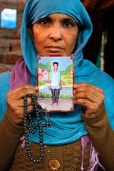 The mother of Mohammad Asif who was shot and killed during protests against Citizenship Amendment Act, holds a photograph of him Dec. 24, 2019, at her residence in Meerut, India.