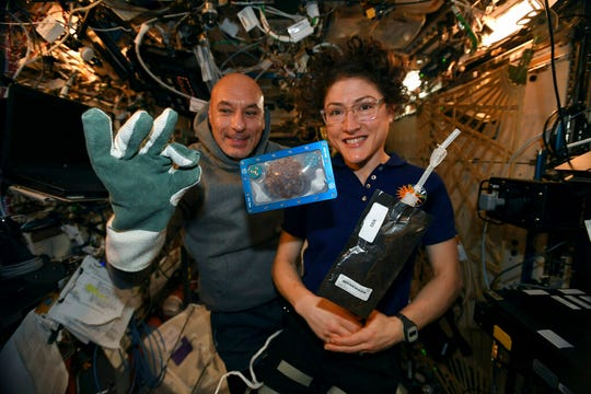 In this photo made available by U.S. astronaut Christina Koch via Twitter on Dec. 26, 2019, she and Italian astronaut Luca Parmitano pose for a photo with a cookie baked on the International Space Station. Researchers want to inspect the handful of chocolate chip cookies baked by astronauts in a special Zero G oven.