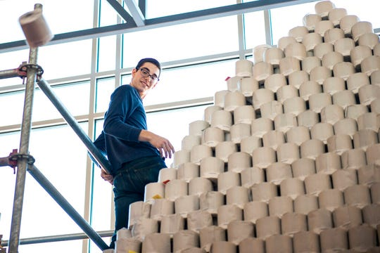 Robotics team captain and program leader Maxton Herst throws the top toilet paper roll off of the world's largest toilet paper pyramid on Monday, Jan. 6, 2020.