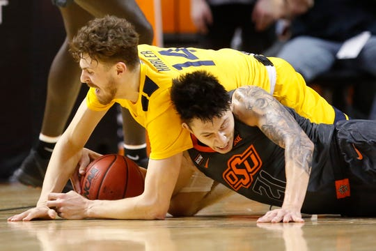 West Virginia guard Chase Harler (14) and Oklahoma State guard Lindy Waters III (21) battle for the ball in the second half.