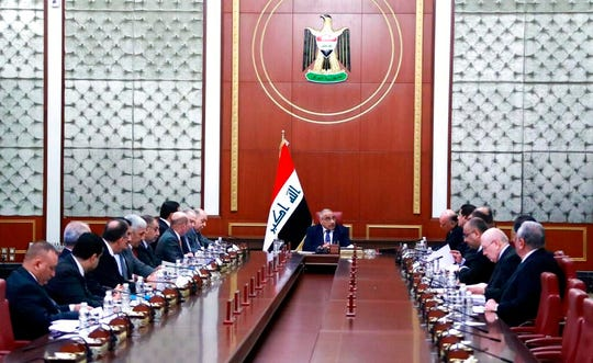 In a photo released by the Iraqi Prime Minister Media Office, Iraqi acting Prime Minister Adil Abdul-Mahdi, center, heads a cabinet meeting at the prime minister's office, in Baghdad, Iraq, Tuesday, Jan. 7, 2020.