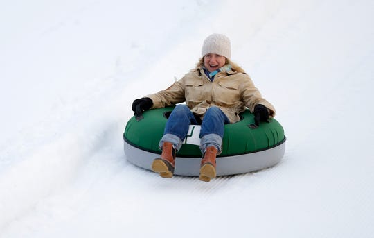 Alison Duke of Barrington smiles as she rides a snow tube down Ariens Hill on Jan. 3. This year's Ariens Free Tubing Night is Feb. 4.