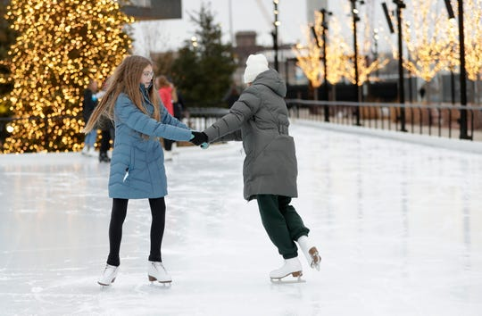 Reese Nystrom and Paisley Wyrzykiewicz of Green Bay ice skate together on the rink at the Titletown District. Free skate lessons are part of the programming this winter.