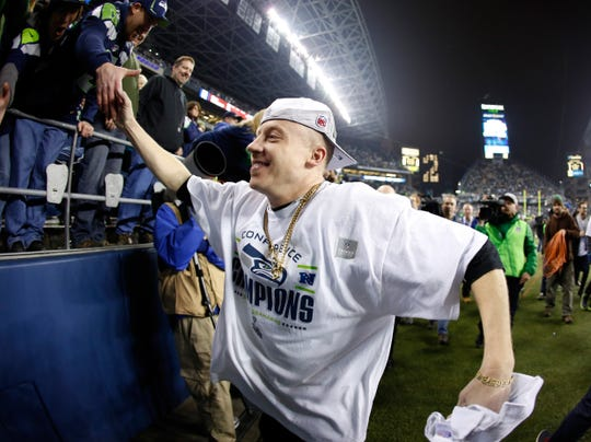 Rapper Macklemore celebrates after the Seattle Seahawks 23-17 victory against the San Francisco 49ers during the 2014 NFC Championship at CenturyLink Field.