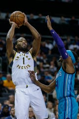 Indiana Pacers forward T.J. Warren, left, shoots over Charlotte Hornets guard Devonte' Graham in the second half of an NBA basketball game in Charlotte, N.C., Monday, Jan. 6, 2020.