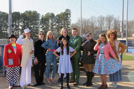 The cast of Matilda takes a photo in front of the baseball stadium at Jackson Christian.