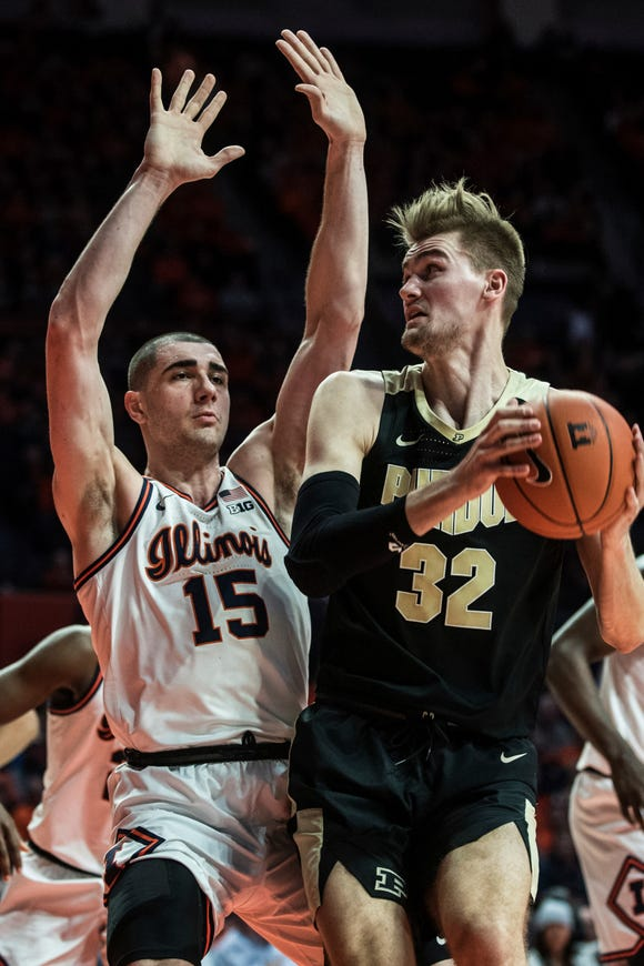 Purdue's Matt Haarms (32) looks to the basket as Illinois' Giorgi Bezhanishvili (15) defends in the second half of an NCAA college basketball game, Sunday, Jan. 5, 2020, in Champaign, Ill. (AP Photo/Holly Hart)