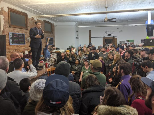 Andrew Yang stands on a counter while speaking to attendees during his event at Perry Perk in Perry, Iowa on Jan. 3, 2020.