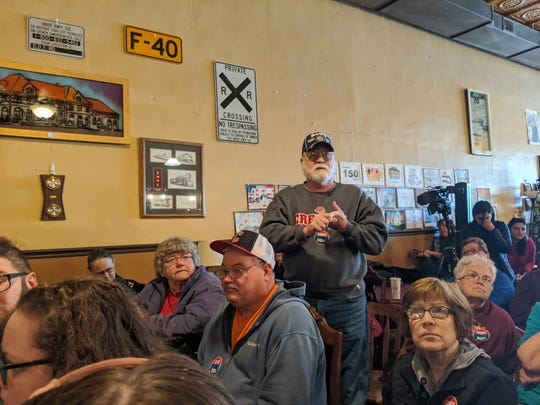 Tom Hawks, an Iowan retiree and navy veteran, stands up to ask a question to Cory Booker during his rally at Adam's Street Espresso Cafe in Creston, Iowa on Jan. 1, 2020.
