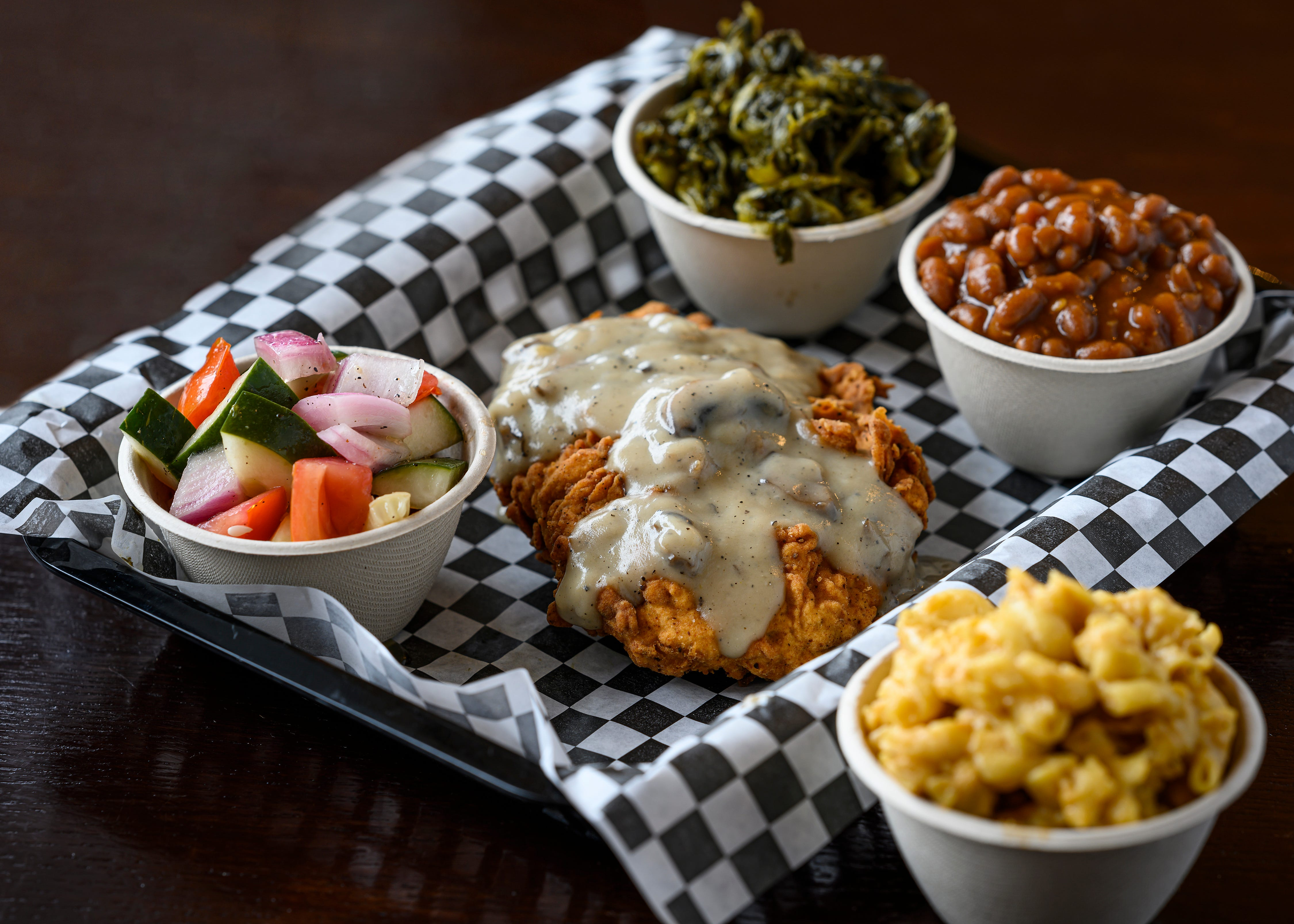 At the Southern V in Nashville, the vegan Chick'n Fried Chick'n with mushroom gravy served with tomato and cucumber salad, turnip greens, baked beans, and mac 'n' cheeze. (Courtesy of Southern V)