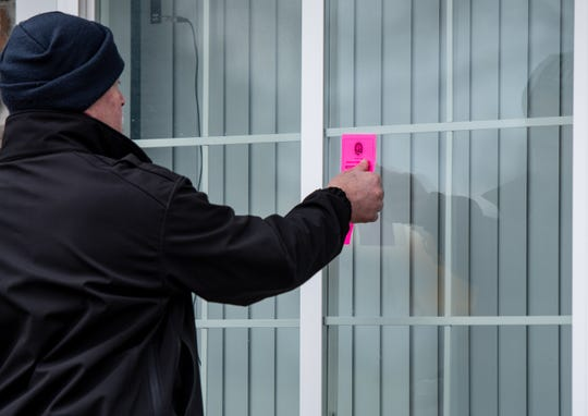 A worker with the City of Lansing Office of Code Compliance places pink tags on units at Capitol Village Apartments Tuesday morning, Jan. 7, 2020. Residents say the tags were removed by management after the city initially posted them Monday.
