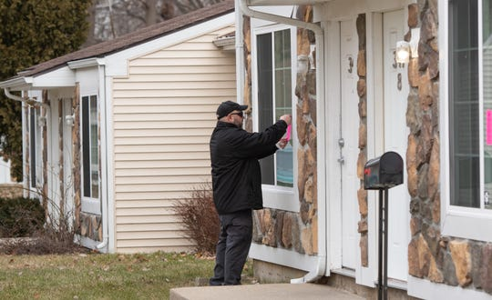 A worker with the City of Lansing's Office of Code Compliance places pink tags on units at Capitol Village Apartments Tuesday morning, Jan. 7, 2020. Residents say the tags were removed by management after the city initially posted them Monday.