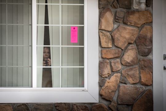 A resident of Capitol Village Apartments watches from her window as workers from the City of Lansing's Office of Code Compliance place pink stickers on housing unit doors and windows Tuesday morning, Jan. 7, 2020. Residents say the tags were removed by management after the city initially posted them Monday.