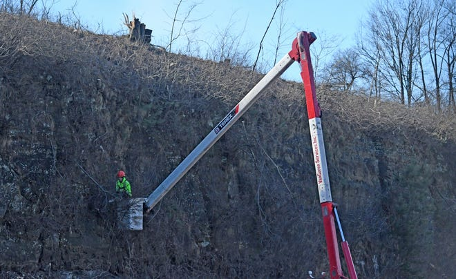 Tree trimmers work high above the U.S. 30 traffic Tuesday afternoon as they clear the brush from the cliffs east of the  Ohio 545 exit.