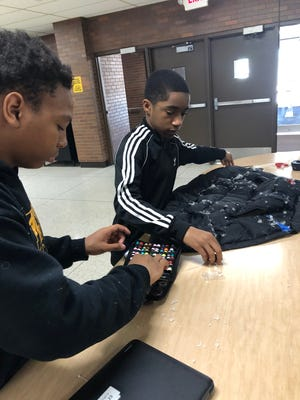 Jayvon McIntyre (left) and Jacobe Cocroft, students at Frank Lloyd Wright Intermediate School in West Allis, create a weighted vest with fidgets attached for a Deeper Learning Project designed to help children with autism.