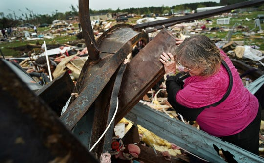 Cindy Rutledge looks for her dachshund in the wreckage of her trailer home on May 17, 2017, in Chetek. The tornado flattened a trailer park, killing one person and injuring 25.