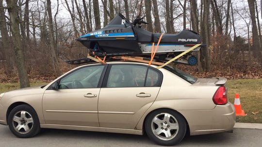 Tommy Mecher didn't have a trailer and wanted to save gas money so he put his 1990 Polaris snowmobile on top of his Chevy Malibu for the trip from Chicago to Bessemer, Michigan, last week.