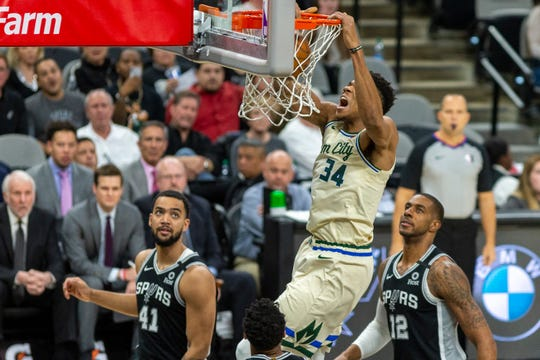 Bucks forward Giannis Antetokounmpo  dunks in front of Spurs forward Trey Lyles Monday night.