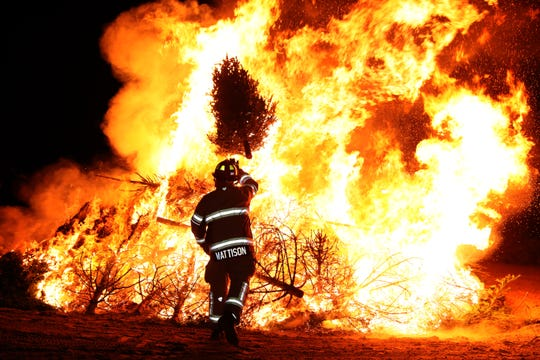 Lt. Kevin Mattison of the Pleasant Prairie Fire Department tosses a tree on the burning pile during a Twelfth Night Christmas tree bonfire on Monday night.
