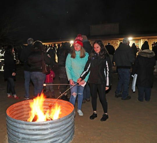 Annika Benton, left, 17, and Ella Lawler, 14, of Kenosha roast marshmallows during Monday night's Twelfth Night Christmas tree bonfire at Lake Andrea.