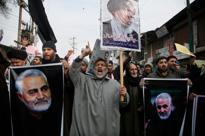 Kashmiri Shiite Muslims shout anti American and anti Israel slogans during a protest against U.S. airstrike in Iraq that killed Iranian Revolutionary Guard Gen. Qassem Soleimani, seen in the photographs, at Magam 37 kilometers (23 miles) north of Srinagar, Indian controlled Kashmir, Friday, Jan. 3, 2020.