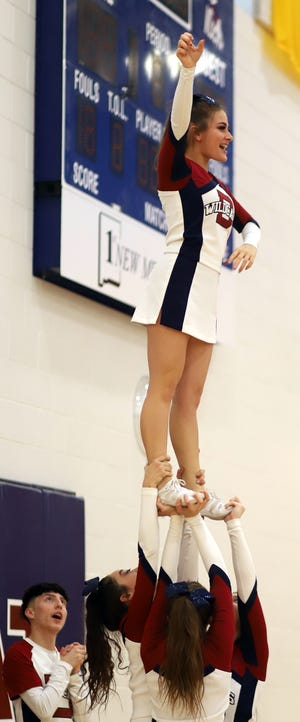 Senior Deming High cheerleader Ciera Wood cheers from the top with help from her varsity teammates during Saturday's Lady Wildcat basketball game at Frank Dooley Court on the campus of Deming High School.
