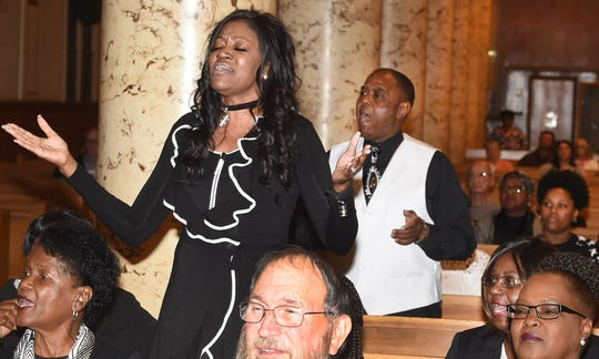 Mercedes Major stands up in prayer while attending the unity prayer service Monday at St. Landry Catholic Church.. She is also a member of the Holy Ghost Choir that performed along with choirs from Morning Star Baptist Church and the Opelousas Community Choir.