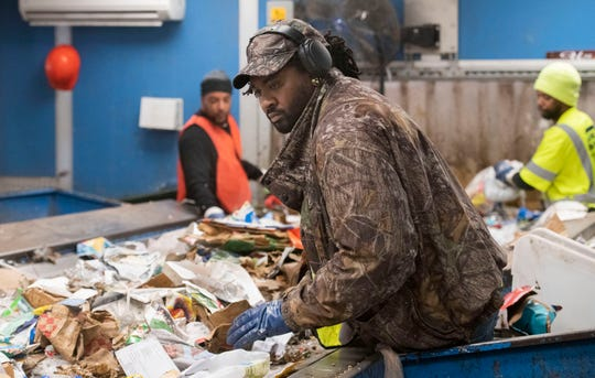 Workers on Tuesday sort thousands of pounds of material at the Emerald Coast Utility Authority's Materials Recycling Facility in Beulah.
