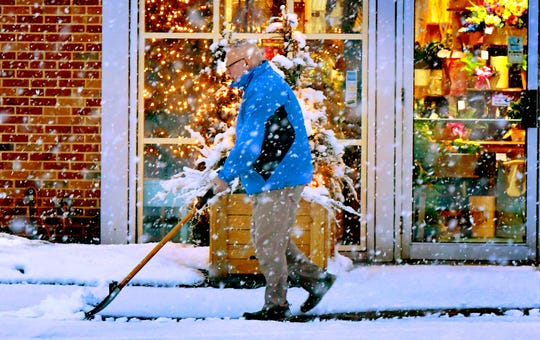 Royer's Flowers employee Woody Felty clears the walkway at the shop on Route 30 in York during a snow shower Tuesday, Jan. 7, 2020. Snow fell throughout York County most of the afternoon. Bill Kalina photo