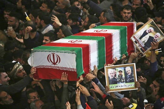 Mourners carry the coffins of slain Iraqi paramilitary chief Abu Mahdi al-Muhandis, Iranian military commander Qasem Soleimani and eight others inside the Shrine of Imam Hussein in the holy Iraqi city of Karbala,during a funeral procession on January 4, 2020. (Mohammed Sawaf/AFP via Getty Images/TNS)