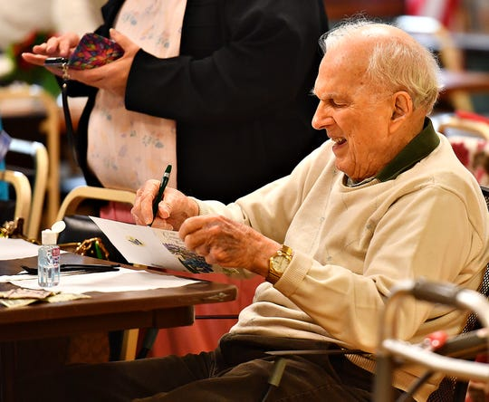 Clem Marchildon, of Shrewsbury Township, signs a group card for another member while the group waits for their lunchtime meal at South Central York County Senior Center in New Freedom, Tuesday, Jan. 7, 2020. Dawn J. Sagert photo