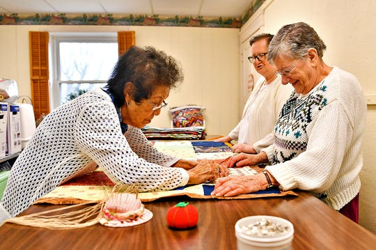 From left, Fuji Smith, Linda Duball, both of Shrewsbury, and Doris Grove of Glen Rock, knot blankets, first assembled, pinned and then delivered by local churches, at South Central York County Senior Center in New Freedom, Tuesday, Jan. 7, 2020. The blankets are then sent to disaster victims. Dawn J. Sagert photo