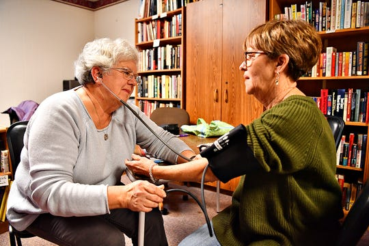 Resident nurse and center board member Judy Flemmens, left, takes a blood pressure reading for Peggy McNally, of Parkton, Md., at South Central York County Senior Center in New Freedom, Tuesday, Jan. 7, 2020. Dawn J. Sagert photo