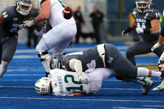 Ohio quarterback Nathan Rourke (12) fumbles after being hit by Nevada's Dom Peterson during the Famous Idaho Potato Bowl at Albertsons Stadium.