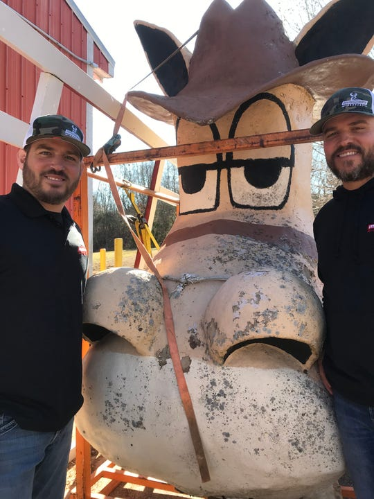 Brothers Brad, left, and Jason Williams pose with Barney, who for many years was on prominent display on the Carpet Barn on Highway 13. Since 2018, the Williams family has operated Midwest Archery at the location, which is north of Springfield.
