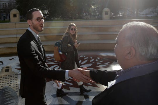 California Sen. Scott Wiener, left, shakes hands with a man after a rally outside City Hall in Oakland on Tuesday. Wiener announced amendments to a closely-watched bill that would allow more housing to be built near public transportation.
