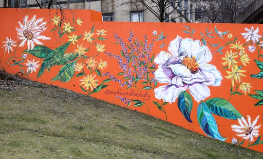 """A new public art mural called """"Orange Joy"""" by Brooklyn artist Surface of Beauty (Natasha May Platt), pictured on the side of the Government Center Garage on New Main Street in Yonkers, was celebrated Jan. 7, 2020. The new mural joins dozens of public art pieces displayed throughout the Yonkers downtown. This 900 square foot mural commissioned by the city, features several wildflowers native to the region. It is designed as a focal point of healing and joy for the community with larger than life blossoming flowers."""
